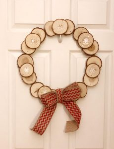 A wood wreath made by gluing wood slices to a large embroidery hoop and adding a homemade burlap wreath