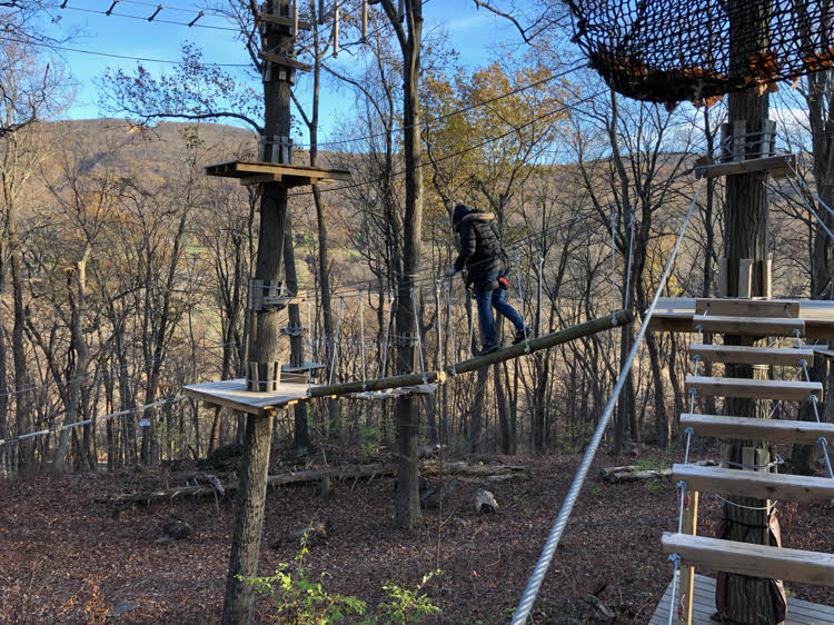 Lauren of Mom Home Guide navigates a lofty obstacle at the TreEscape course at Mountain Creek