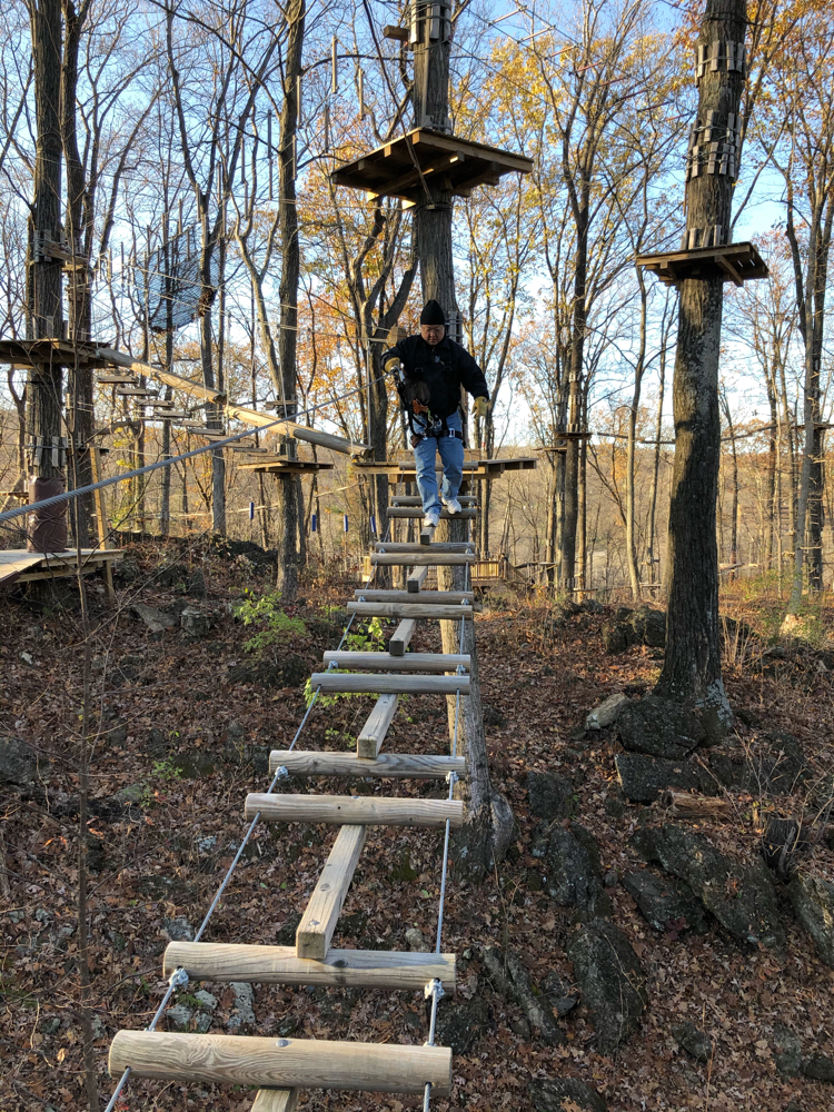 A guest crossing an obstacle at the TreEscape Aerial Adventure Ropes Course at Mountain Creek