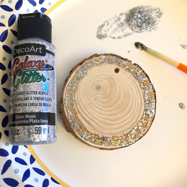 A wood slice painted with Galaxy Glitter in moon-silver by DecoArt