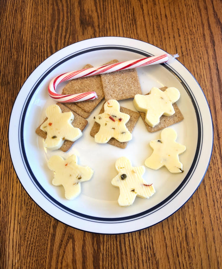A festive platter of cheese and crackers for the holidays. The cheese is cut with mini cookie cutters