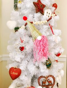 A white Christmas tree decorated with DIY gnome ornaments and hearts for Valentine's Day.
