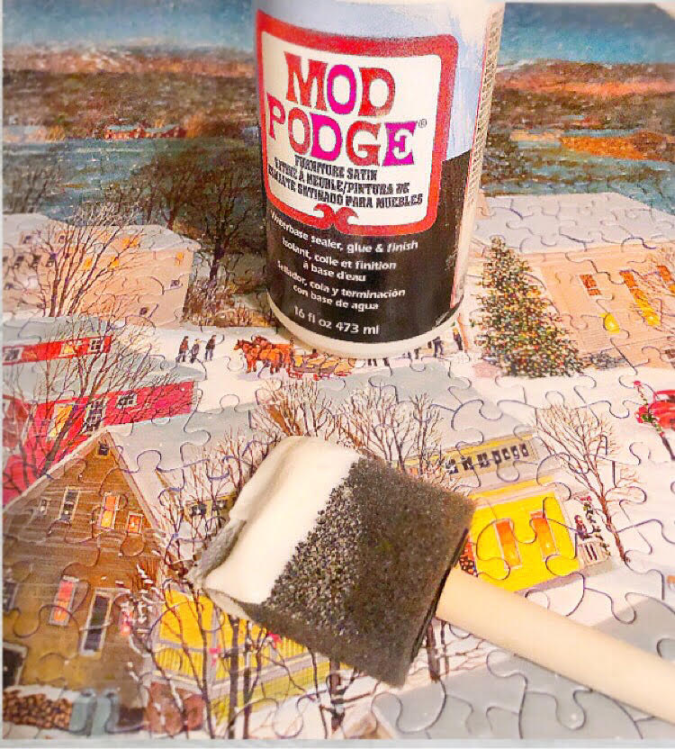 how to glue a jigsaw puzzle together with Mod Podge and a foam craft brush. Shown is a jigsaw puzzle of Stowe, Vermont