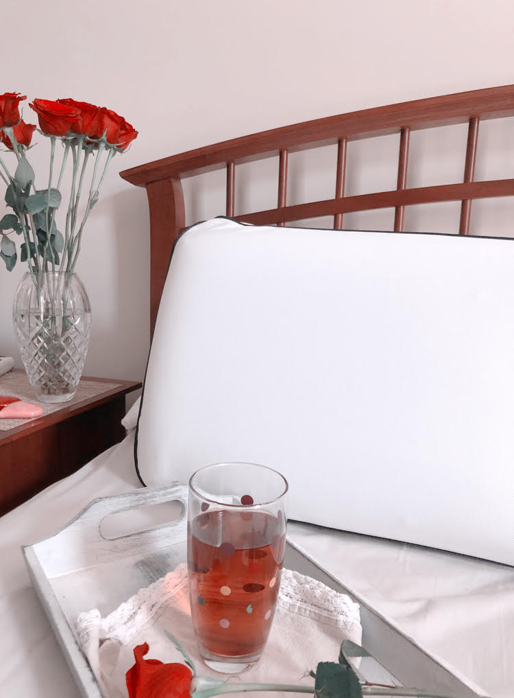 A farmhouse style bed with a cooling memory foam pillow. A vase of roses on a nightstand. A tray with a glass of iced tea.