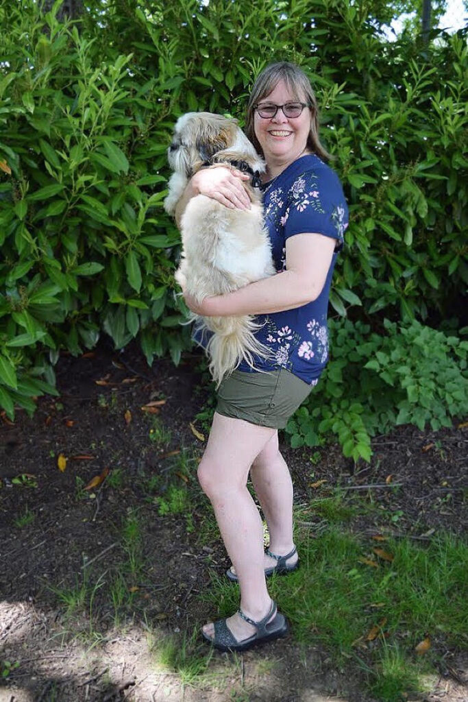 Woman in a blue floral top wearing olive shorts and grey sandals and holding a Shih Tzu.