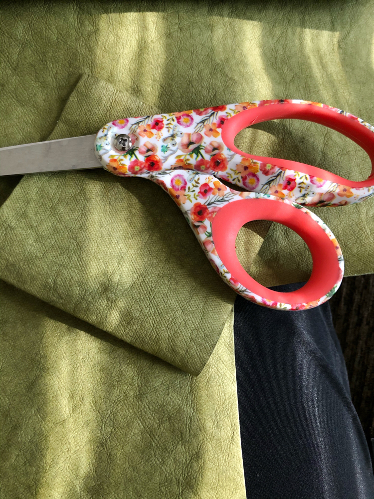 Use a sharp pair of sewing scissors to cut Kraft tex, which is a paper that acts like fabric and looks like leather.