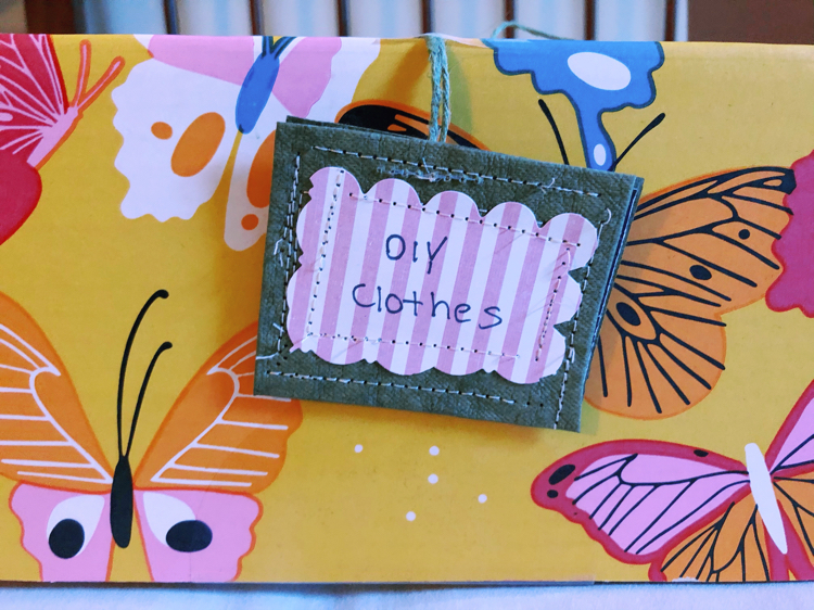 A colorful box with a diy organizing tag for organizing clothes