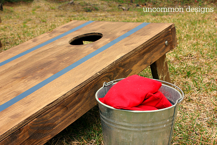 Cornhole board stained brown with painted blue stripes. A bucket of beanbags is next to the board. Photo by Uncommon Designs
