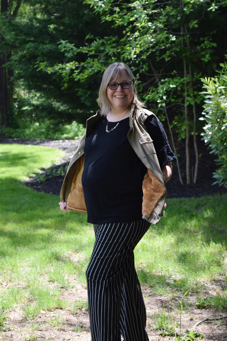 A woman wearing a faux fur lined utility vest with a pair of wide legged black and white striped pants.
