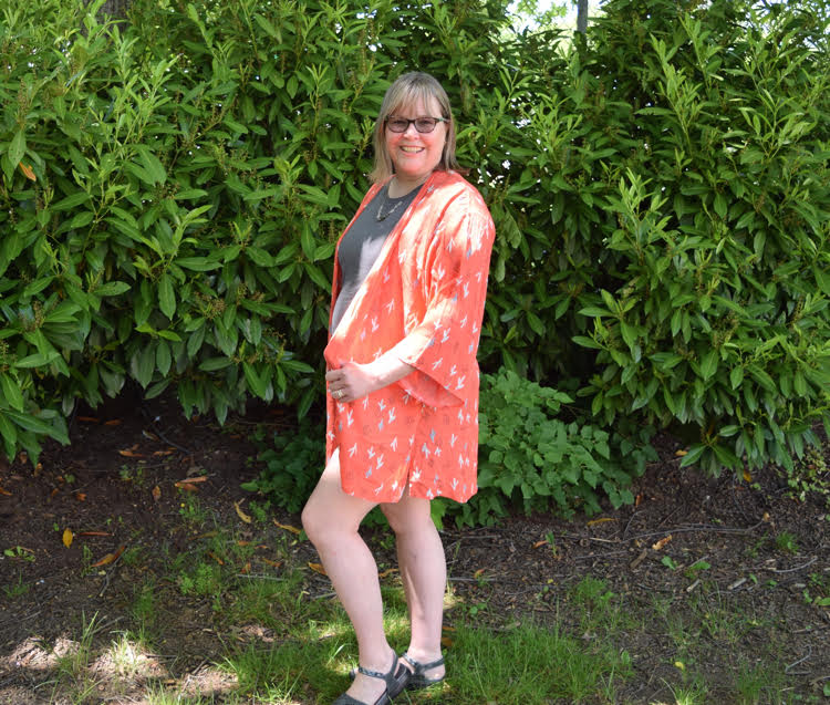 Woman wearing a grey T shirt, a peach kimono with a cacti print and gray sandals.