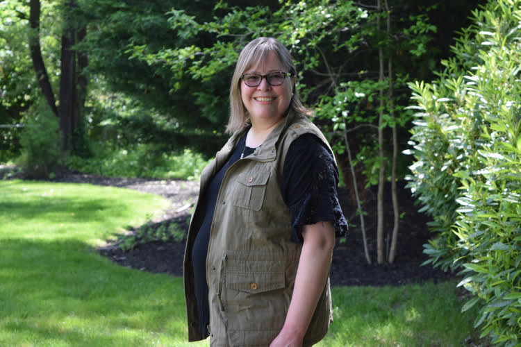 A woman models an olive colored utility vest in a backyard