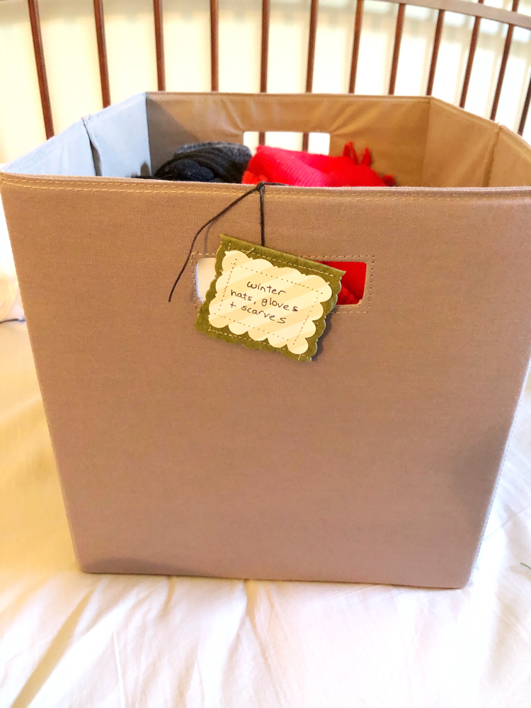 A storage bin of clothes with a DIY organizing tag