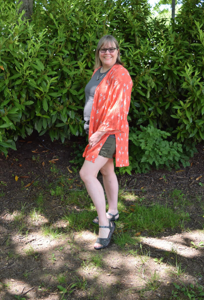 A woman models a peach colored kimono, a gray T shirt, olive shorts and gray sandals.