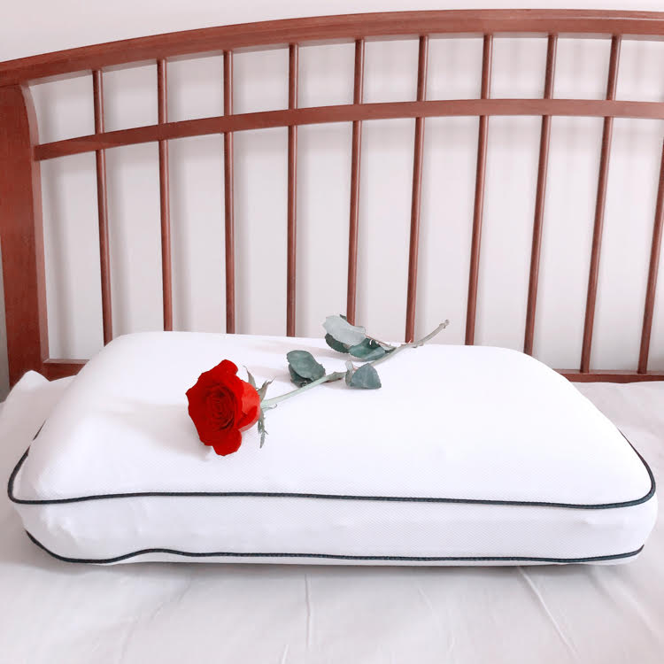 A farmhouse style bed with a memory foam cooling pillow  from Bed, Bath & Beyond with a rose on top.
