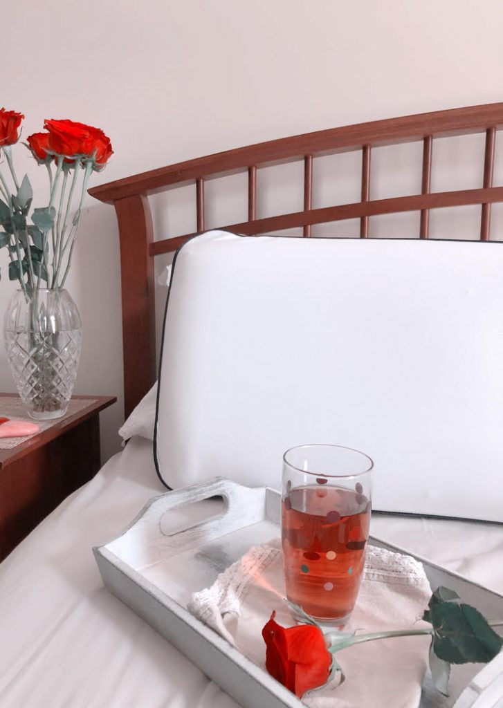 Cooling memory foam pillow on a farmhouse style bed with a crystal vase of roses on a bedside table.