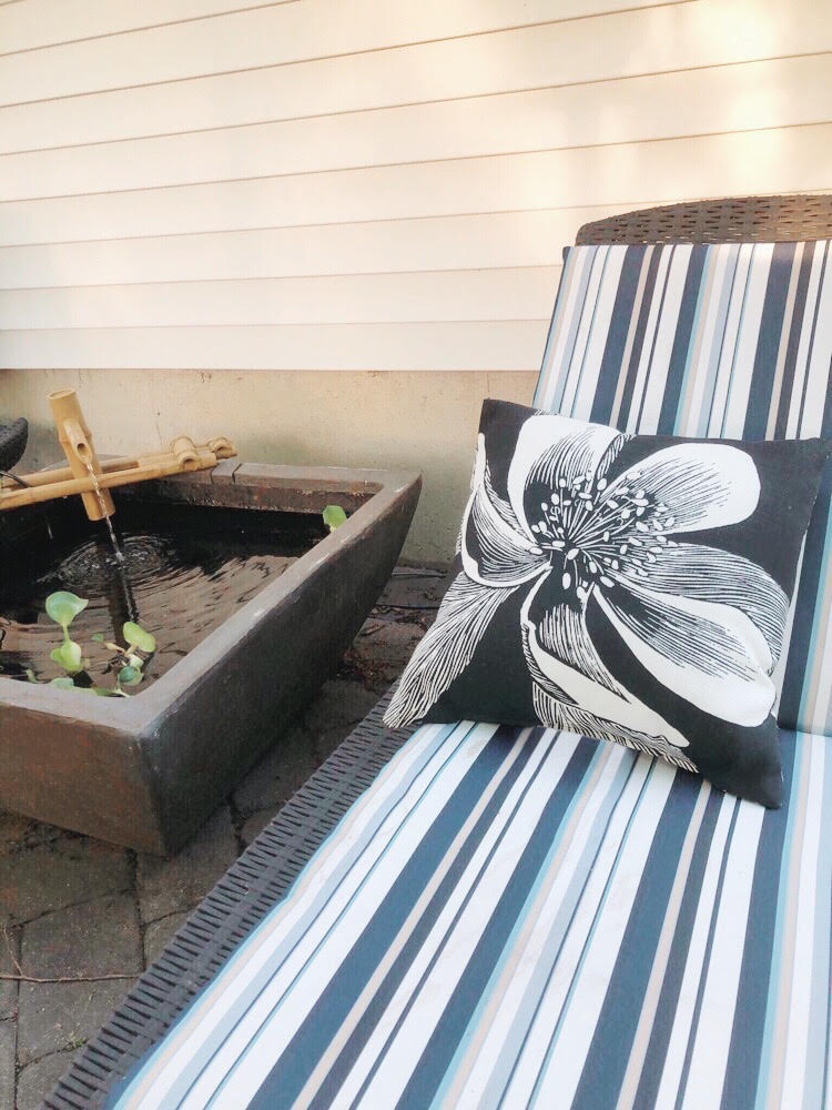 Chaise lounge with a blue and white striped cushion and a black pillow with a flower print. A patio pond with a fountain and water hyacinths is nearby on the paver patio.