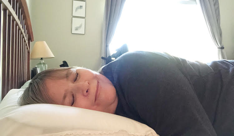 Woman sleeping on a cooling memory foam pillow from Bed, Bath & Beyond.