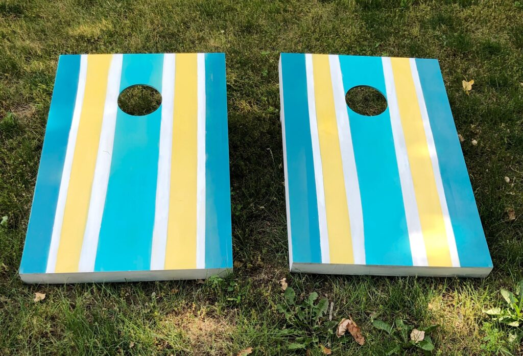 DIY spray painted corn hole boards  with blue and yellow stripes