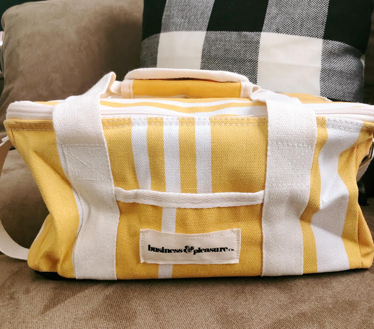 Yellow and white striped yellow cooler bag for carrying a picnic or cool drinks.