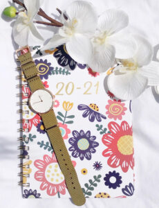 beautiful watch with a green nylon strap on a pretty datebook accented with colorful flowers