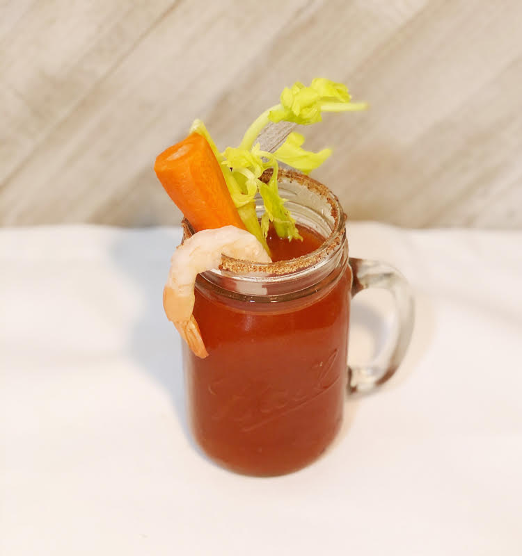 Overhead shot of a Bloody Mary garnished with shrimp, carrot and celery. The glass is rimmed with salt, pepper and other spices.