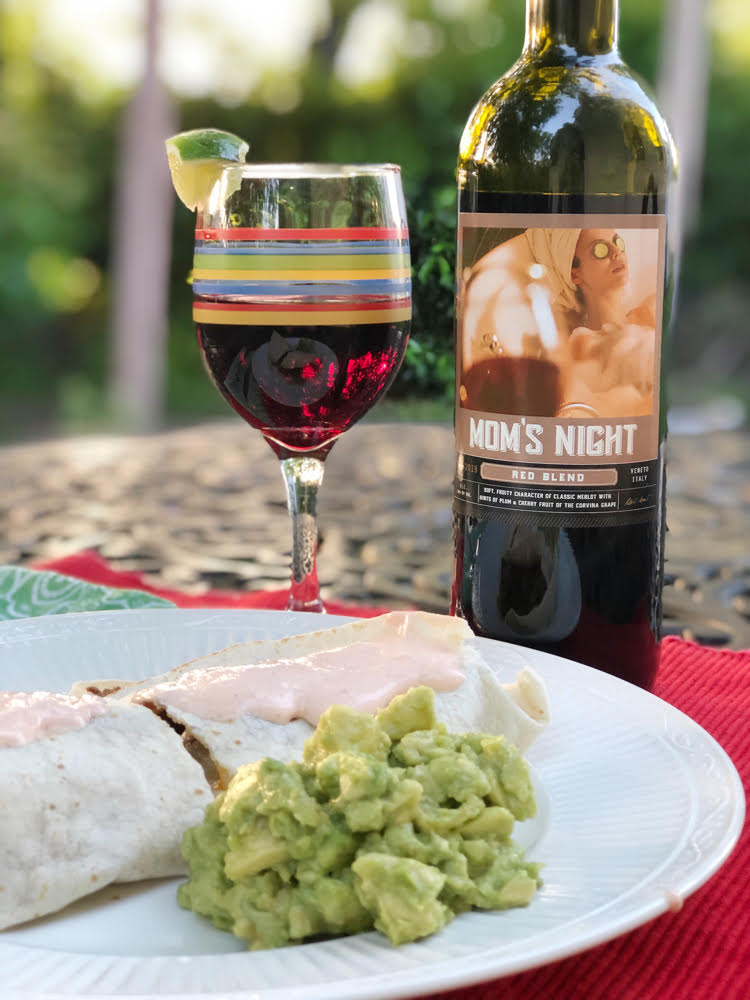 Mom's night red wine with a quesadilla and a side of guacamole on a wrought-iron table on an outdoor patio
