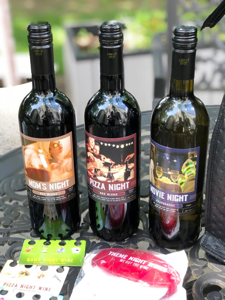 Bottles of Mom's Night, Pizza Night and Movie Night Wines from Theme Night Wines on a wrought iron patio table.