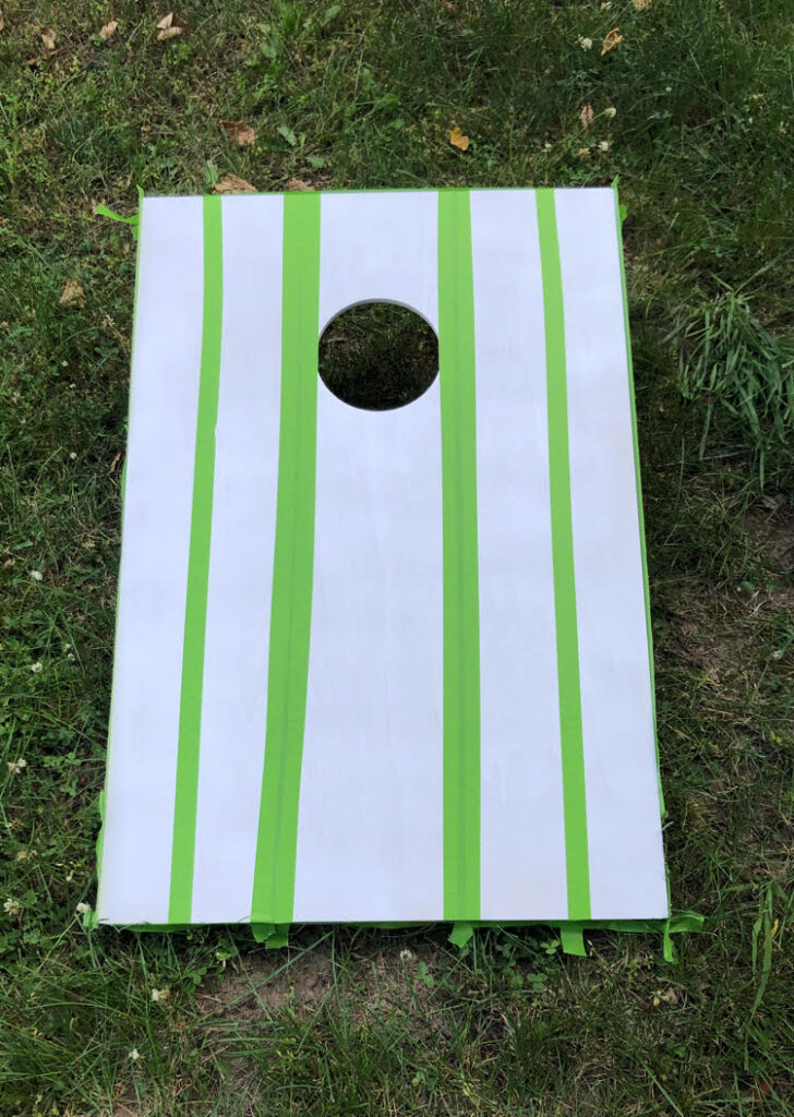 Frog Tape on a corn hole board to create painted stripes.