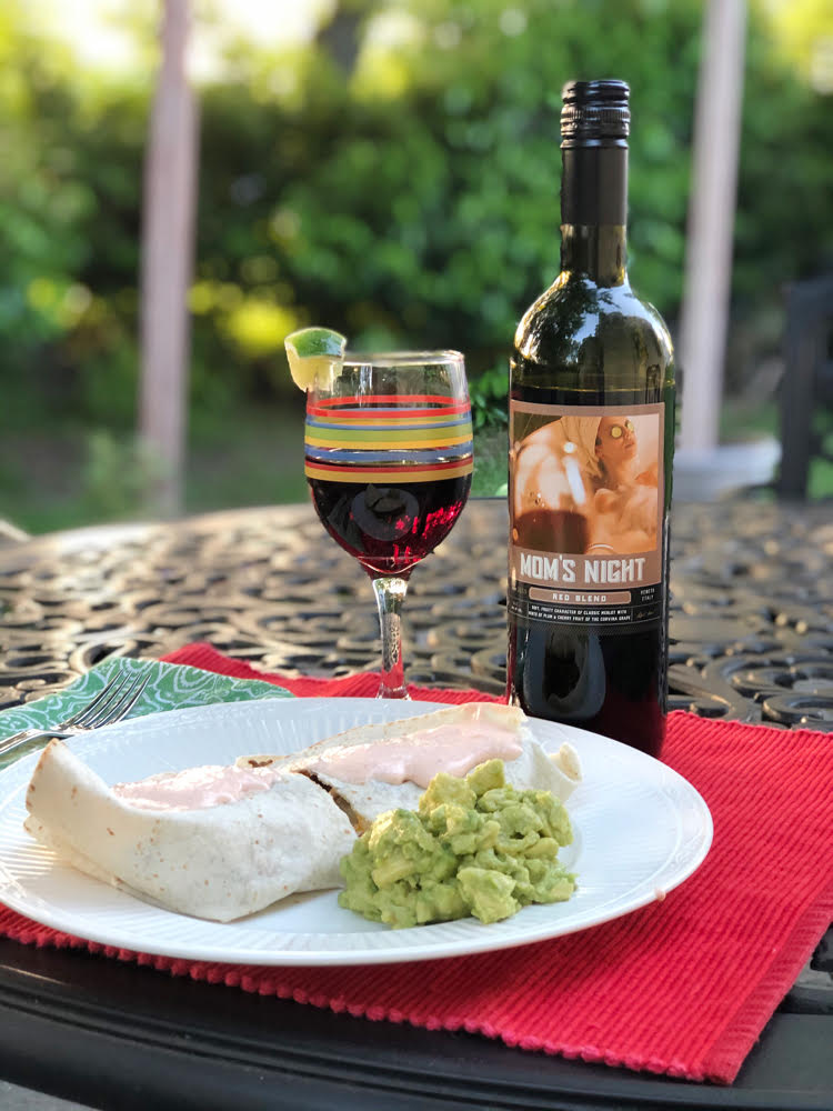 A glass of Mom's Night red wine with a plate that holds a quesadilla and fresh guacamole on an outdoor table.