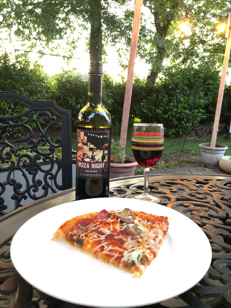Pizza Night wine with a slice of pepperoni and mushroom pizza on a wrought iron patio table.