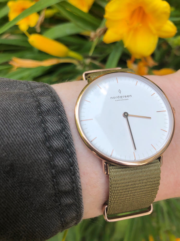 A Nordgreen rose gold watch with a green nylon strap against some pretty yellow lilies