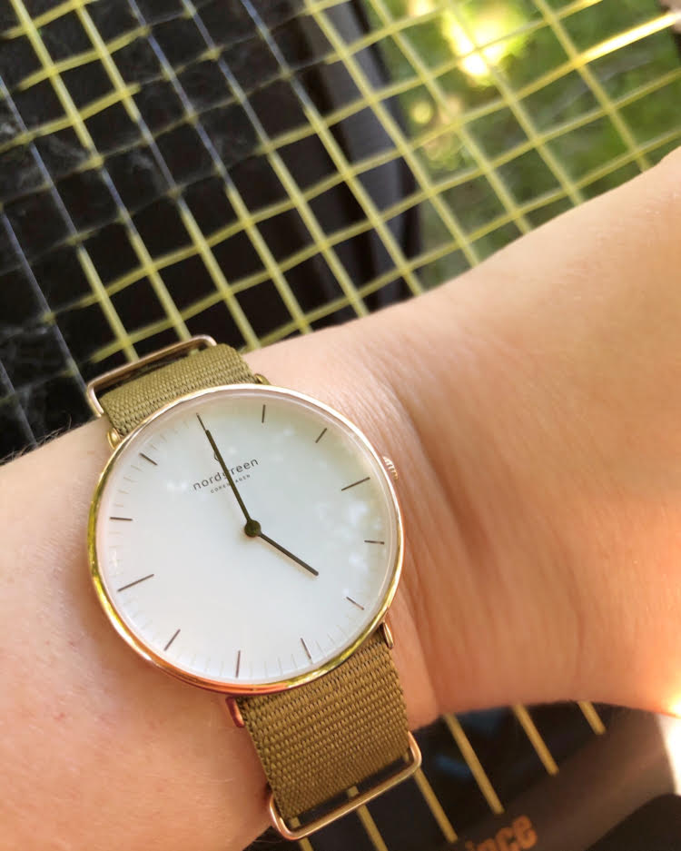 Pretty Nordgreen watch with a white face and a green nylon strap against a tennis racket