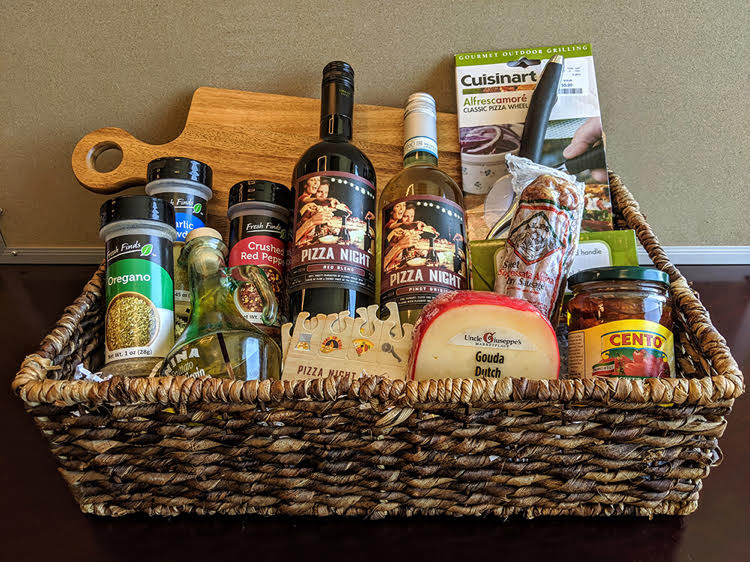 A pizza night gift basket idea by Theme Night Wines. The basket is filled with ingredients and supplies for making homemade pizza.