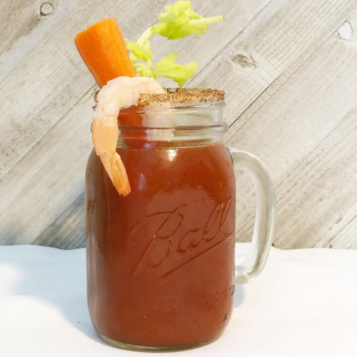 A Bloody Mary in a Ball Jar with a carrot and celery stick and a cooked shrimp