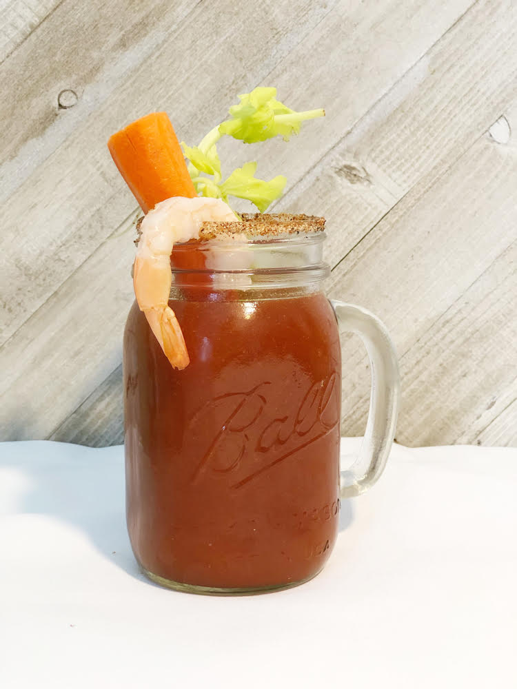 A Bloody Mary in a Ball mason jar glass. The drink is garnished with celery, a carrot stick and a shrimp.
