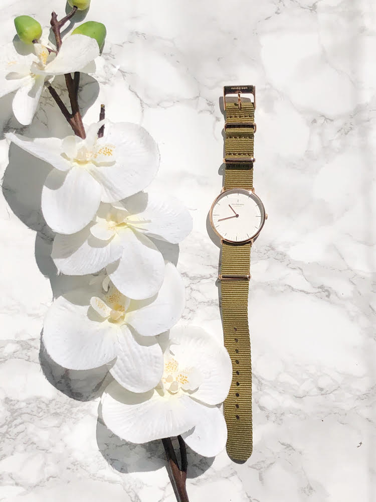 A rose gold watch with a white face and a green nylon band on a marble surface with white flowers
