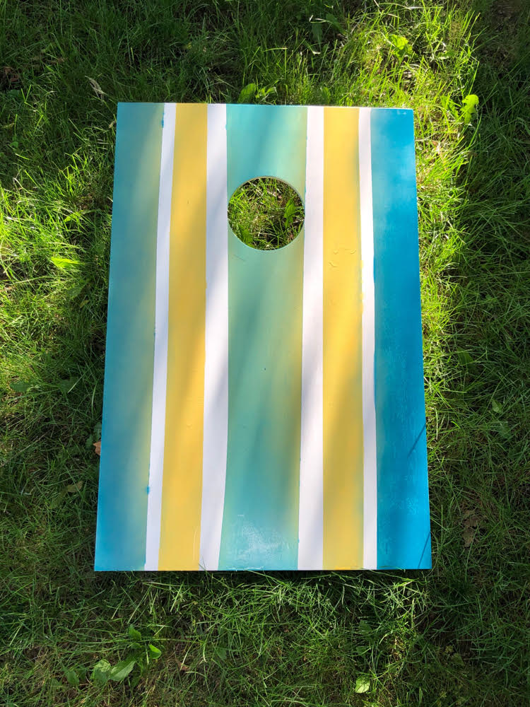 corn hole board spray painted with green, yellow and blue stripes