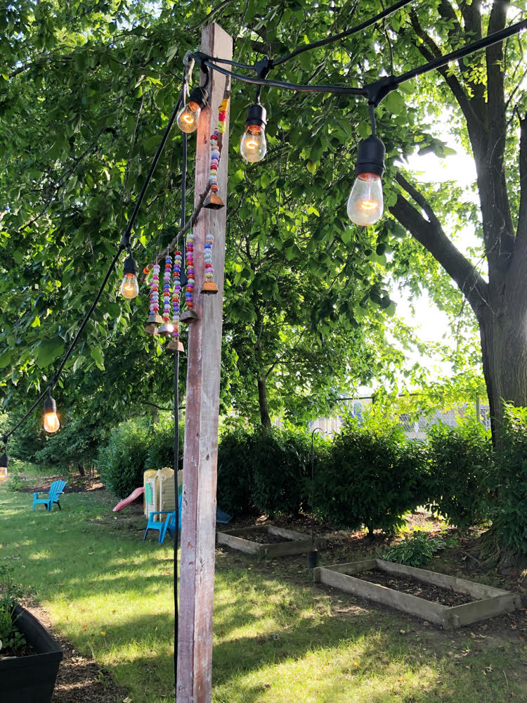 String lights strung from DIY planter poles - one pole is decorated with DIY wind chimes made with beads and mini cow bells