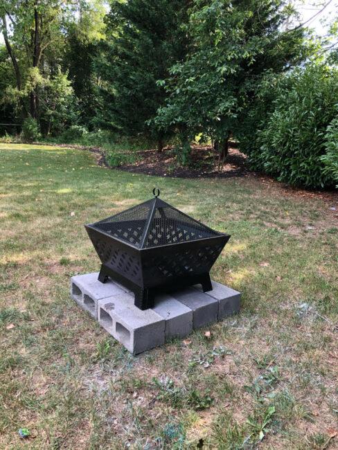 a beautiful Landmann metal fire pit on a base of concrete blocks