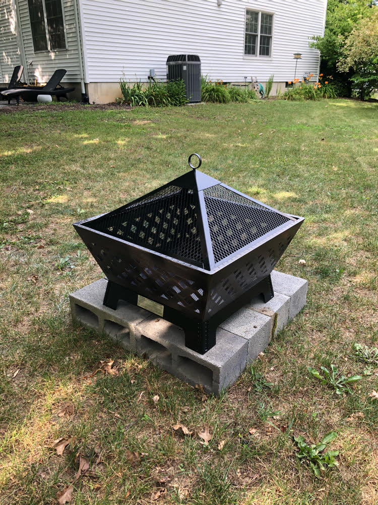 "An antique bronze Landmann 24"" fire pit set on a square of concrete blocks in a backyard."