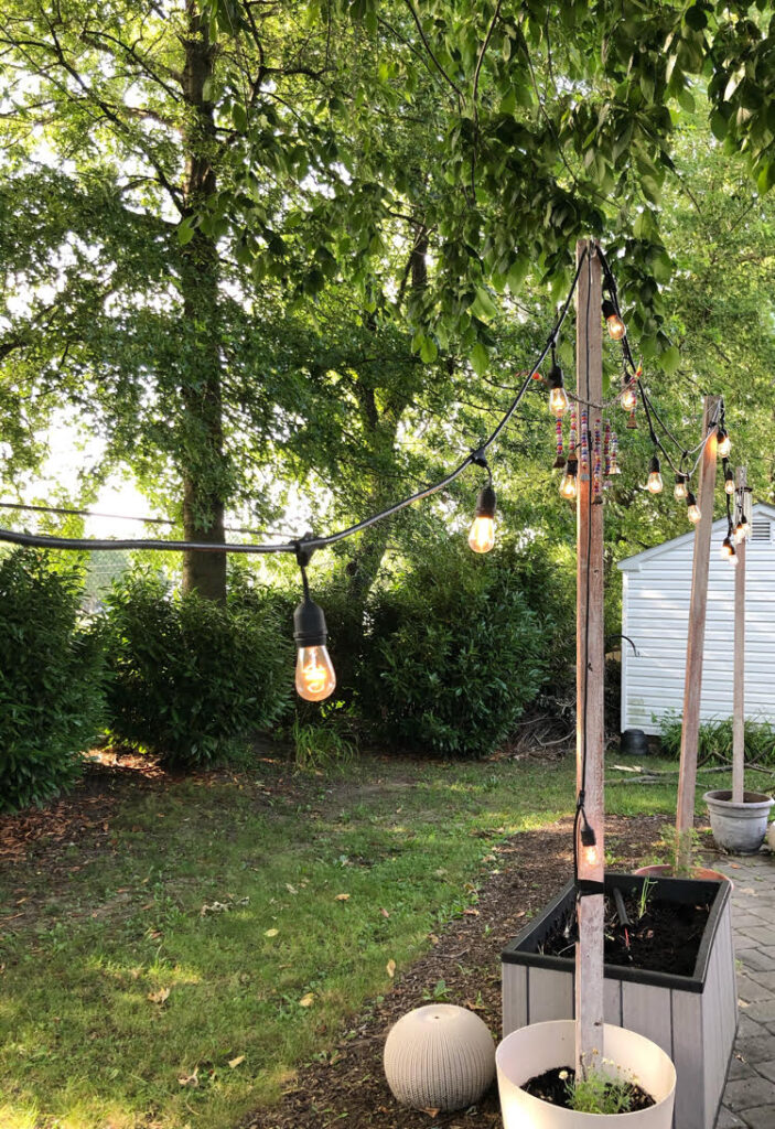 a gray paver patio with Edison style patio string lights strung on DIY planter string light poles
