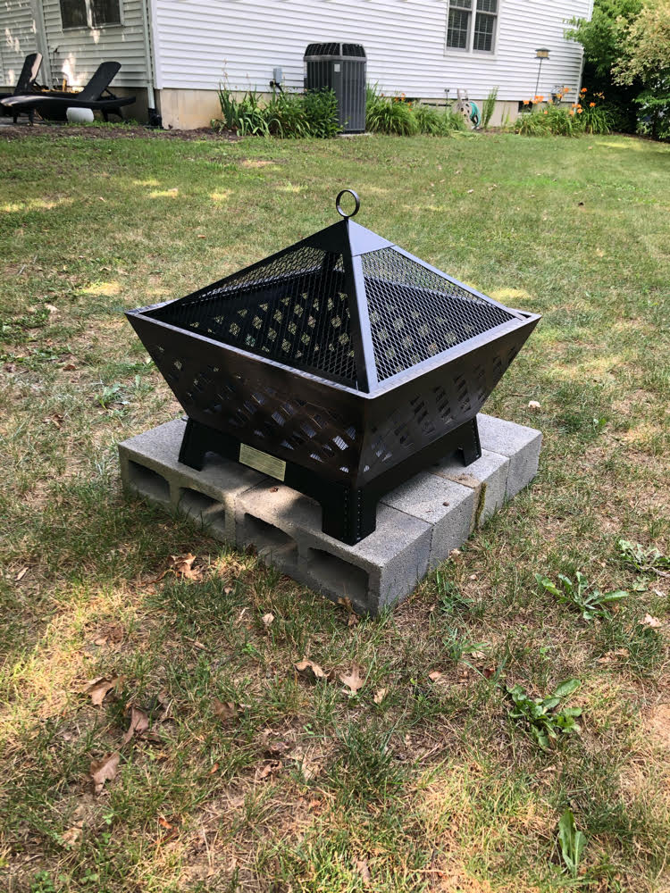 A Landmann metal fire pit with a spark screen sitting on a DIY base of concrete blocks in a backyard