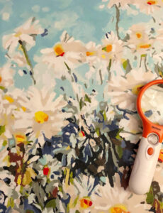 magnifying glass on a painted paint by numbers canvas of daisies