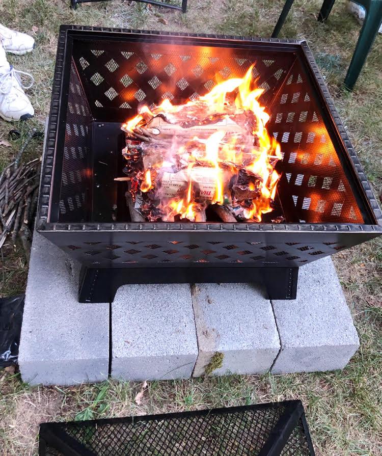 Logs burning in a metal fire pit in a backyard.