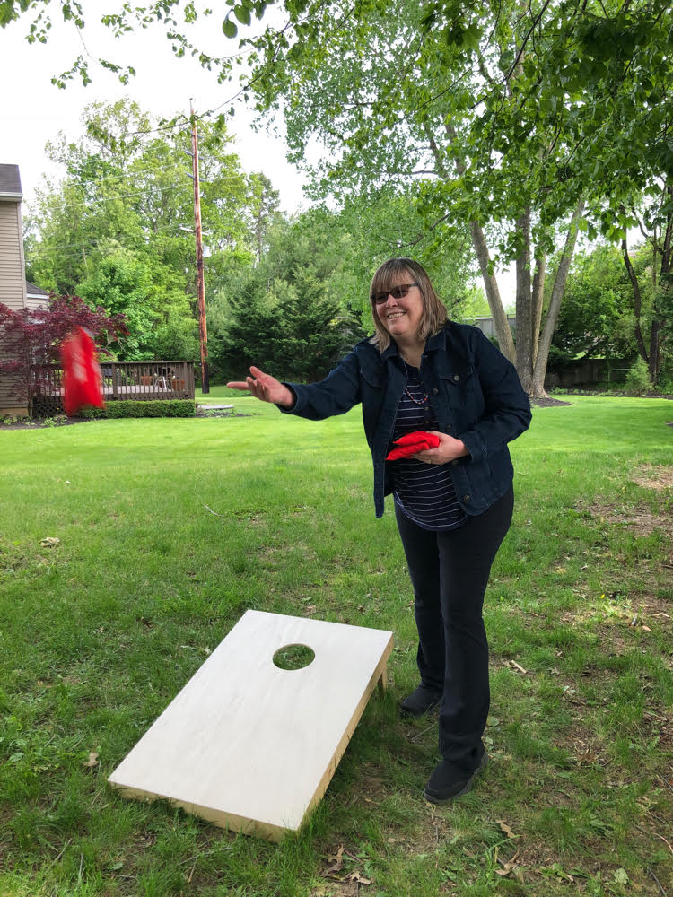 Lauren of Mom Home Guide tosses a bean bag while standing by a corn hole board.