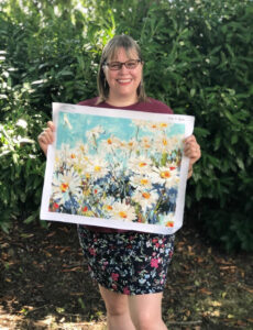 Woman holding a completed paint by numbers painting of daisies