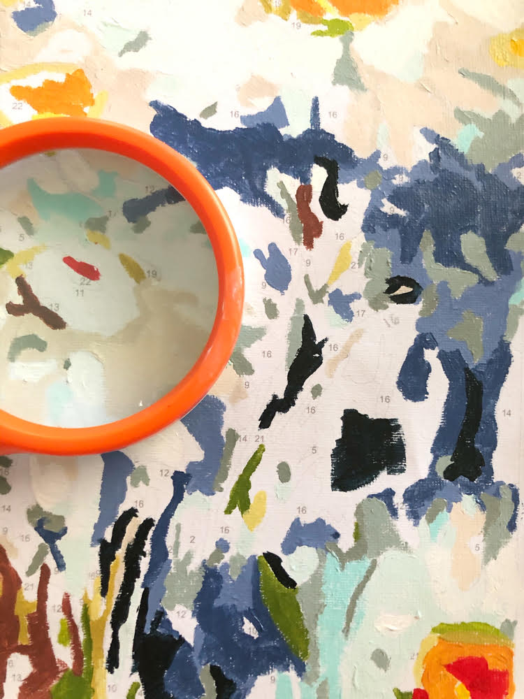 close up shot of a paint by numbers canvas magnified by an orange magnifying glass