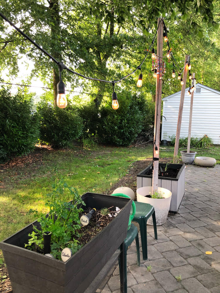 Gray paver patio with DIY string light posts and a raised garden