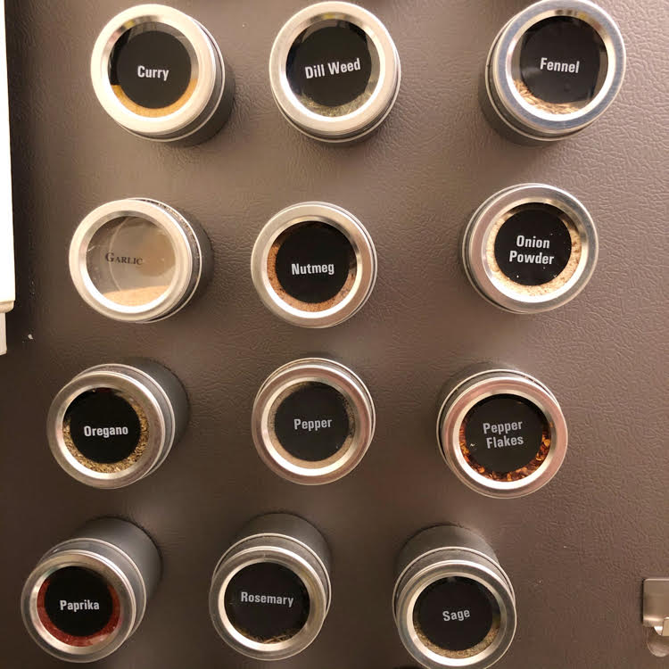 magnetic tins filled with spices on a refrigerator
