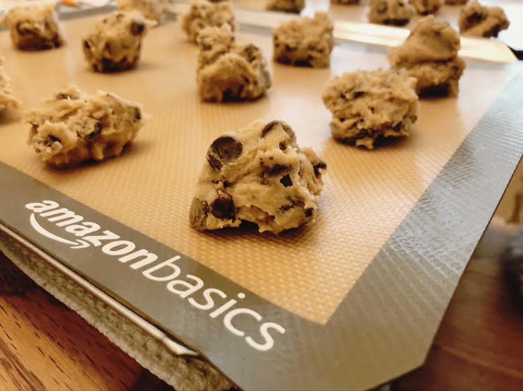balls of chocolate chip cookie dough on a silicone baking mat